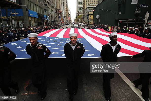 Members of the US Navy march with the American Flag in the the nation's largest Veterans Day Parade in New York City on November 11 2015 in New York...