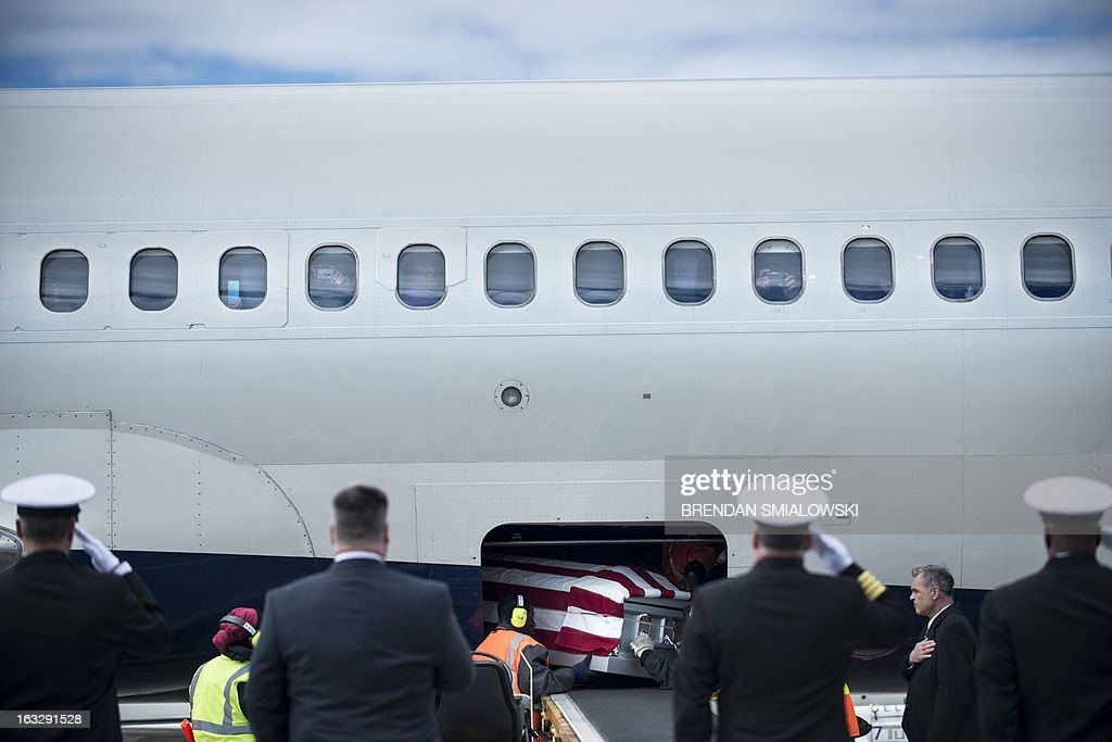 Members of the US Navy watch as ground crew remove a casket with the remains of a US Civil War casualty from Delta Flight 1172 during a dignified transfer at Dulles International Airport March 7, 2013 in Sterling, Virginia. The remains of two unknown soldiers found inside the sunken iron clad ship, the USS Monitor, were transfered for burial at Arlington National Cemetery after being discovered in 2002 and being sent to Joint POW/MIA Accounting Command in Hawaii for possible genetic identification. AFP PHOTO/Brendan SMIALOWSKI