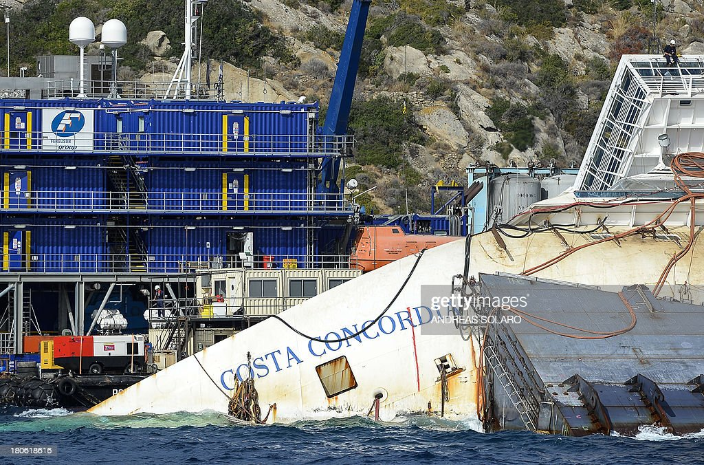 Members of the US salvage company Titan and Italian firm Micoperi work at the wreck of Italy's Costa Concordia cruise ship near the harbour of Giglio Porto on September 15, 2013. Salvage workers will attempt to raise the cruise ship on September 16, 2013, weather permitting, in the largest and most expensive maritime salvage operation in history, so-called 'parbuckling', to rotated the ship by a series of cables and hydraulic machines. Thirty-two people died when the ship, with 4,200 passengers onboard, hit rocks and ran aground off the island of Giglio on January 2012.