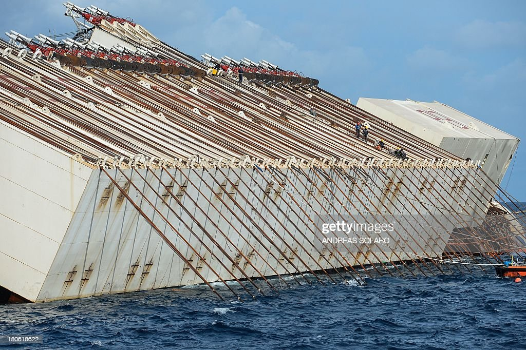 Members of the US salvage company Titan and Italian firm Micoperi work at the wreck of Italy's Costa Concordia cruise ship near the harbour of Giglio Porto on September 15, 2013. Salvage workers will attempt to raise the cruise ship on September 16, 2013, weather permitting, in the largest and most expensive maritime salvage operation in history, so-called 'parbuckling', to rotated the ship by a series of cables and hydraulic machines. Thirty-two people died when the ship, with 4,200 passengers onboard, hit rocks and ran aground off the island of Giglio on January 2012. AFP PHOTO / ANDREAS SOLARO