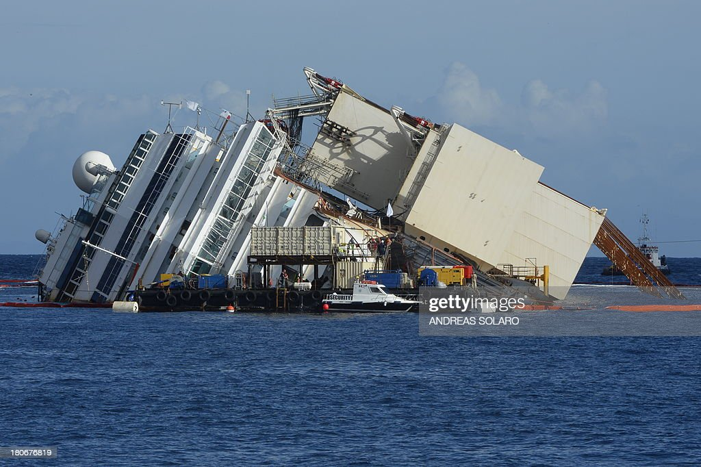Members of the US salvage company Titan and Italian firm Micoperi work at the wreck of Italy's Costa Concordia cruise ship near the harbour of Giglio Porto on September 16, 2013. Salvage workers will attempt to raise the cruise ship today, in the largest and most expensive maritime salvage operation in history, so-called 'parbuckling', to rotated the ship by a series of cables and hydraulic machines. Thirty-two people died when the ship, with 4,200 passengers onboard, hit rocks and ran aground off the island of Giglio on January 2012. AFP PHOTO / ANDREAS SOLARO
