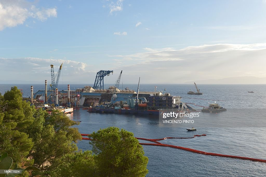 Members of the US salvage company Titan and Italian firm Micoperi work at the wreck of Italy's Costa Concordia cruise ship near the harbour of Giglio Porto on September 16, 2013. Salvage workers will attempt to raise the cruise ship today, in the largest and most expensive maritime salvage operation in history, so-called 'parbuckling', to rotated the ship by a series of cables and hydraulic machines. Thirty-two people died when the ship, with 4,200 passengers onboard, hit rocks and ran aground off the island of Giglio on January 2012. AFP PHOTO / VINCENZO PINTO