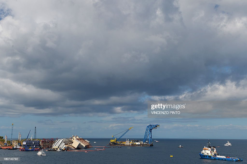 Members of the US salvage company Titan and Italian firm Micoperi work at the wreck of Italy's Costa Concordia cruise ship near the harbour of Giglio Porto on September 16, 2013. Salvage workers attempt to raise the cruise ship today in the largest and most expensive maritime salvage operation in history, so-called 'parbuckling', to rotated the ship by a series of cables and hydraulic machines. Thirty-two people died when the ship, with 4,200 passengers onboard, hit rocks and ran aground off the island of Giglio on January 2012. AFP PHOTO / VINCENZO PINTO