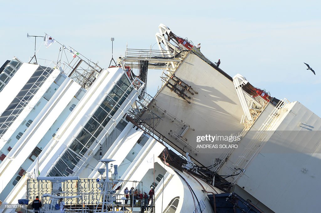 Members of the US salvage company Titan and Italian firm Micoperi work at the wreck of Italy's Costa Concordia cruise ship near the harbour of Giglio Porto on September 16, 2013. Salvage workers attempt to raise the cruise ship today in the largest and most expensive maritime salvage operation in history, so-called 'parbuckling', to rotated the ship by a series of cables and hydraulic machines. Thirty-two people died when the ship, with 4,200 passengers onboard, hit rocks and ran aground off the island of Giglio on January 2012.