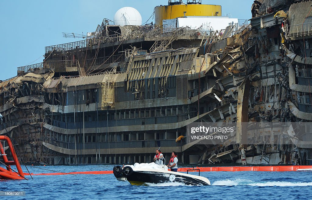 Members of the US salvage company Titan and Italian firm Micoperi pass by the destroyed side of the wreckage of Italy's Costa Concordia cruise ship which begins to emerge from water near the harbour of Giglio Porto. Salvage operators in Italy lifted the Costa Concordia cruise ship upright from its watery grave off the island of Giglio in the biggest ever project of its kind. The ship's horn sounded for the first time since the January 13, 2012 tragedy, its sound mixing with applause and cheers in the port in a dramatic climax to the massive salvage operation. Local residents and survivors spoke of an eerie feeling as the ship rose, saying the sight reminded them of the tragedy that claimed 32 lives.