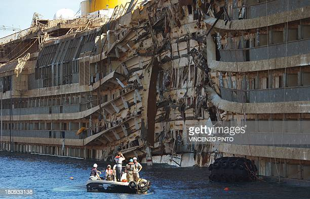 Members of the US salvage company Titan and Italian firm Micoperi inspect on September 18 the wreck of Italy's Costa Concordia cruise ship after...