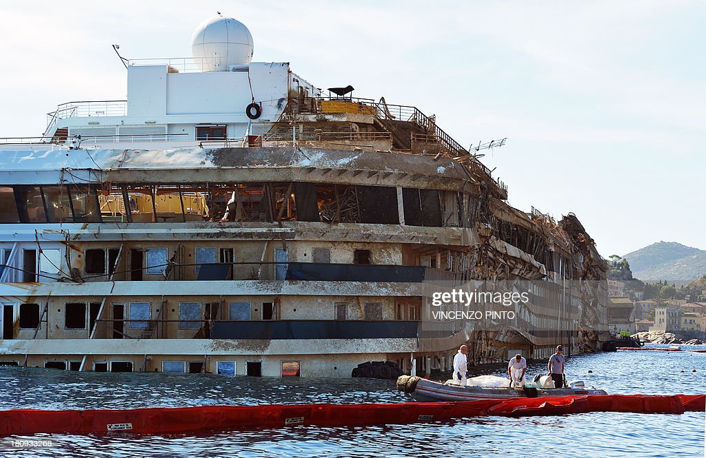 Members of the US salvage company Titan and Italian firm Micoperi inspect on September 18, 2013, the wreck of Italy's Costa Concordia cruise ship after emerging from water, near the harbour of Giglio Porto. Salvage operators in Italy lifted the Costa Concordia cruise ship upright from its watery grave off the island of Giglio in the biggest ever project of its kind. The ship was upright for the first time since the January 13, 2012 tragedy, and led to applause and cheers in the port, in a dramatic climax to the massive salvage operation. Local residents and survivors spoke of an eerie feeling as the ship rose, saying the sight reminded them of the tragedy that claimed 32 lives..