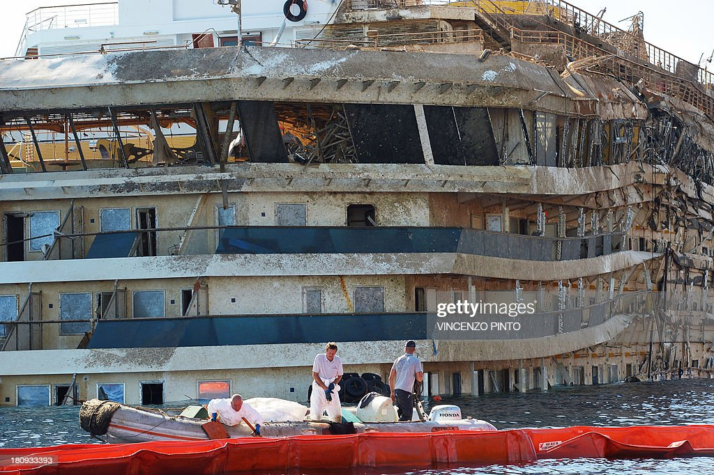 Members of the US salvage company Titan and Italian firm Micoperi inspect on September 18, 2013, the wreck of Italy's Costa Concordia cruise ship after emerging from water, near the harbour of Giglio Porto. Salvage operators in Italy lifted the Costa Concordia cruise ship upright from its watery grave off the island of Giglio in the biggest ever project of its kind. The ship was upright for the first time since the January 13, 2012 tragedy, and led to applause and cheers in the port, in a dramatic climax to the massive salvage operation. Local residents and survivors spoke of an eerie feeling as the ship rose, saying the sight reminded them of the tragedy that claimed 32 lives.