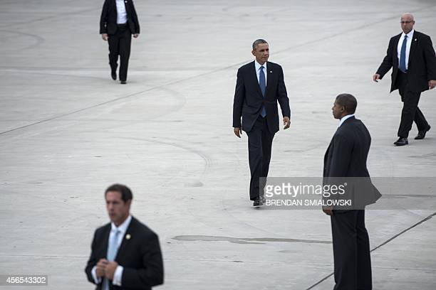 Members of the US Secret Service escort US President Barack Obama as he walks to Air Force One at Gary Chicago International Airport on October 2...