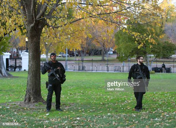 Members of the US Secret Service stand guard in the north lawn as first lady Melania Trump and her son Barron welcomed a 195foot balsam Fir that will...