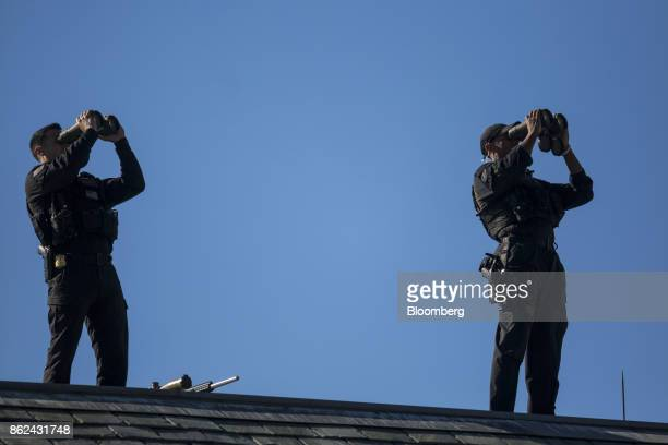 Members of the US Secret Service use binoculars while standing on the roof of the West Wing of the White House in Washington DC US on Tuesday Oct 17...
