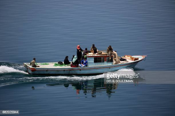 Members of the USbacked Syrian Democratic Forces made up of an alliance of Arab and Kurdish fighters sail a boat carrying displaced and wounded...