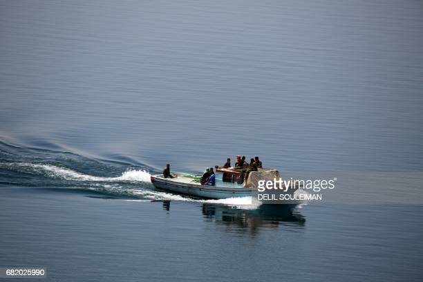 Members of the USbacked Syrian Democratic Forces made up of an alliance of Arab and Kurdish fighters drive a boat carrying displaced and wounded...