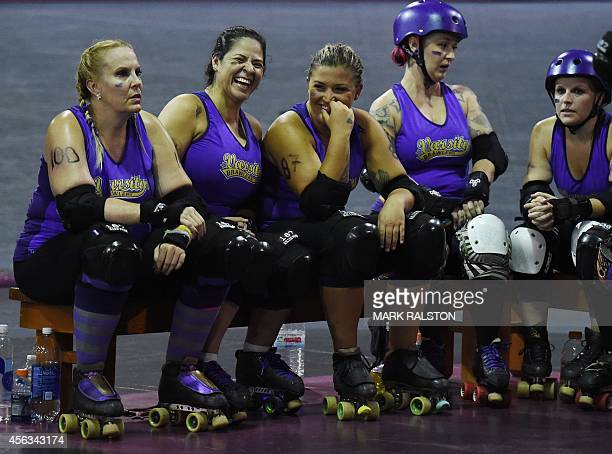 Members of the Varsity Brawlers rest during their match against the Sirens during the LA Derby Dolls women's banked track roller derby event in Los...