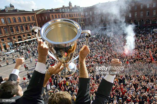 Members of the victorius Toulouse rugby team celebrate with the European cup in front of their supporters on the balcony of the Hotel de ville in...