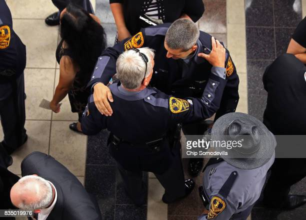 Members of the Virginia State Police and other law enforcement officers from across the country greet one another before the funeral for TrooperPilot...