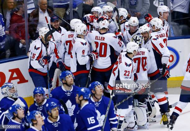 Members of the Washington Capitals celebrate as members of the Toronto Maple Leafs watch the replay after Marcus Johansson of the Washington Capitals...