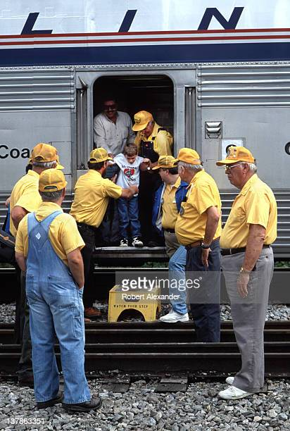 Members of the Watauga Valley Chapter of the National Railway Historical Society in Johnson City Tennessee help a young excursion passenger exit the...