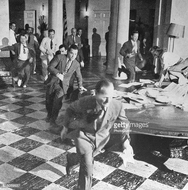 Members of the White House Press Corps rush to telephones after President Harry Truman's announcement of the surrender of Japan and the end of World...