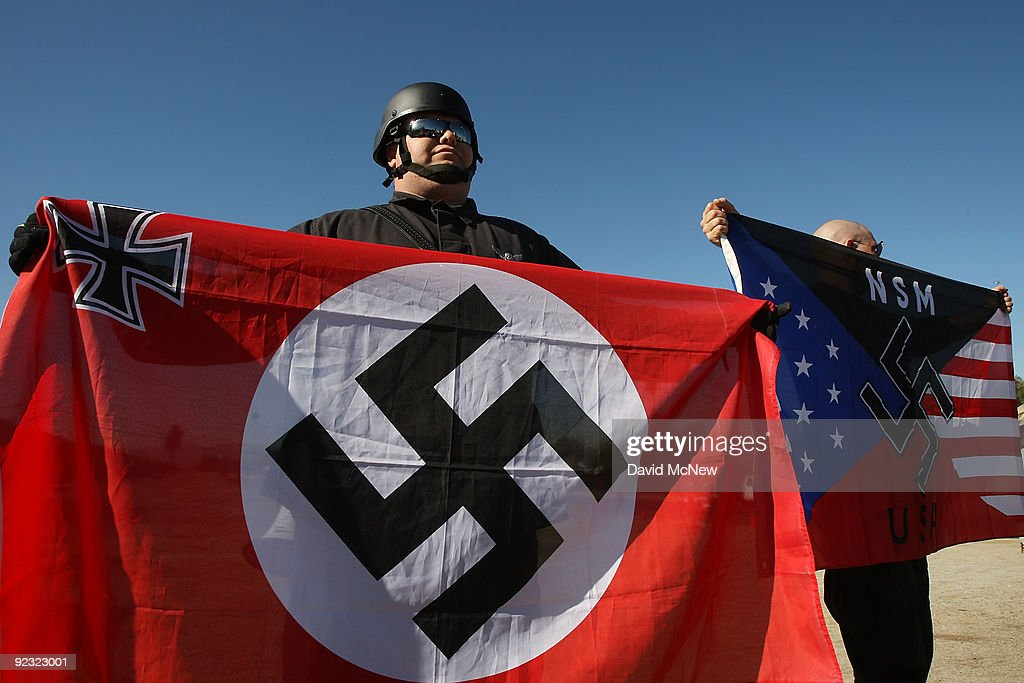 Members of the white supremacist group the National Socialist Movement hold swastika flags at the NSMÕs antiillegal immigration rally near a Home...