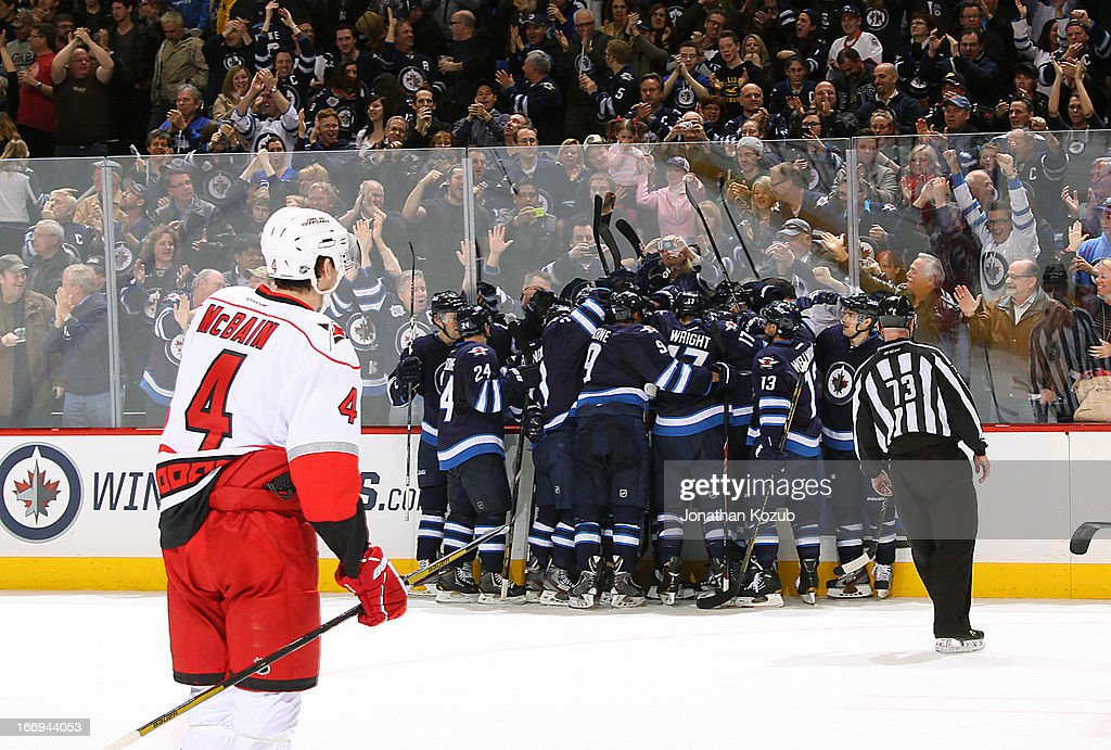 Members of the Winnipeg Jets celebrate an overtime victory as Jamie McBain #4 of the Carolina Hurricanes skates by dejectedly at the MTS Centre on April 18, 2013 in Winnipeg, Manitoba, Canada.