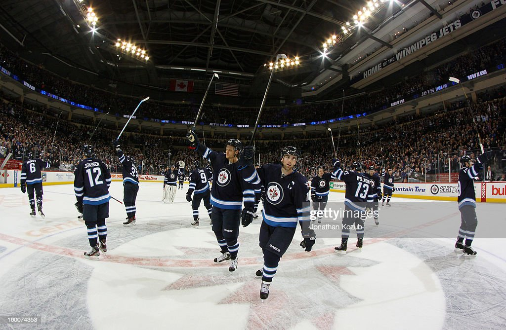 Members of the Winnipeg Jets gather at centre ice to salute the fans following a 4-2 victory over the Pittsburgh Penguins at the MTS Centre on January 25, 2013 in Winnipeg, Manitoba, Canada.