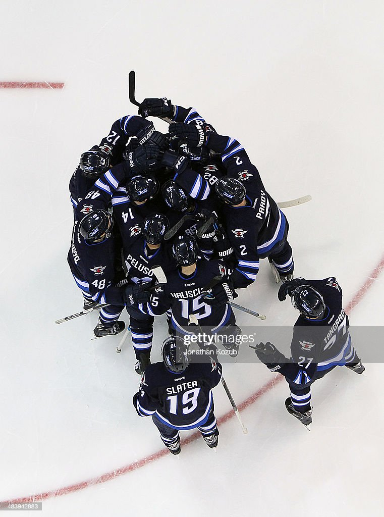 Members of the Winnipeg Jets mob teammate Michael Hutchinson #34 (not shown) after he backstopped the team to a 2-1 shootout victory over the Boston Bruins at the MTS Centre on April 10, 2014 in Winnipeg, Manitoba, Canada.