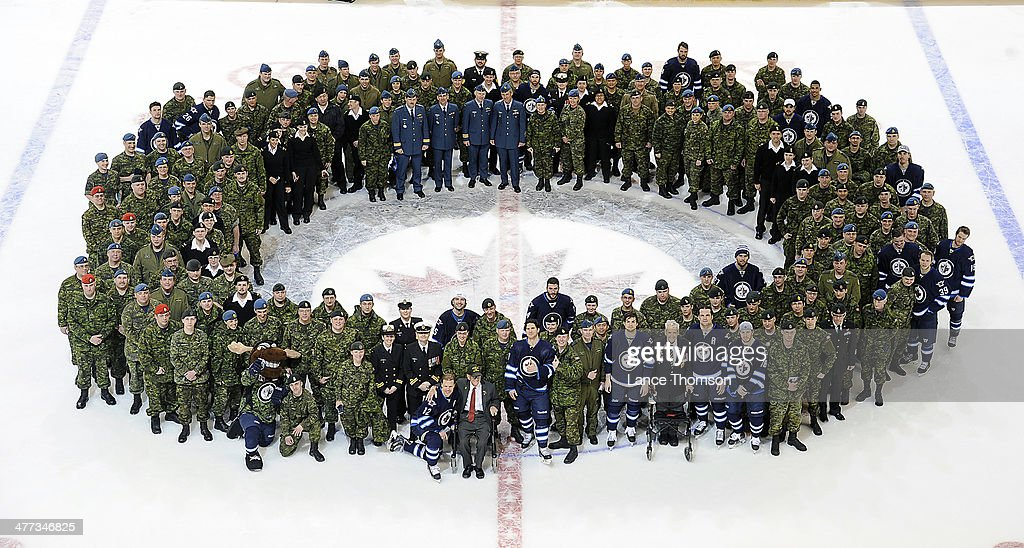 Members of the Winnipeg Jets posed at centre ice with members of the Canadian Armed Forces following NHL action against the Ottawa Senators as military personnel was honored at the MTS Centre on March 8, 2014 in Winnipeg, Manitoba, Canada.