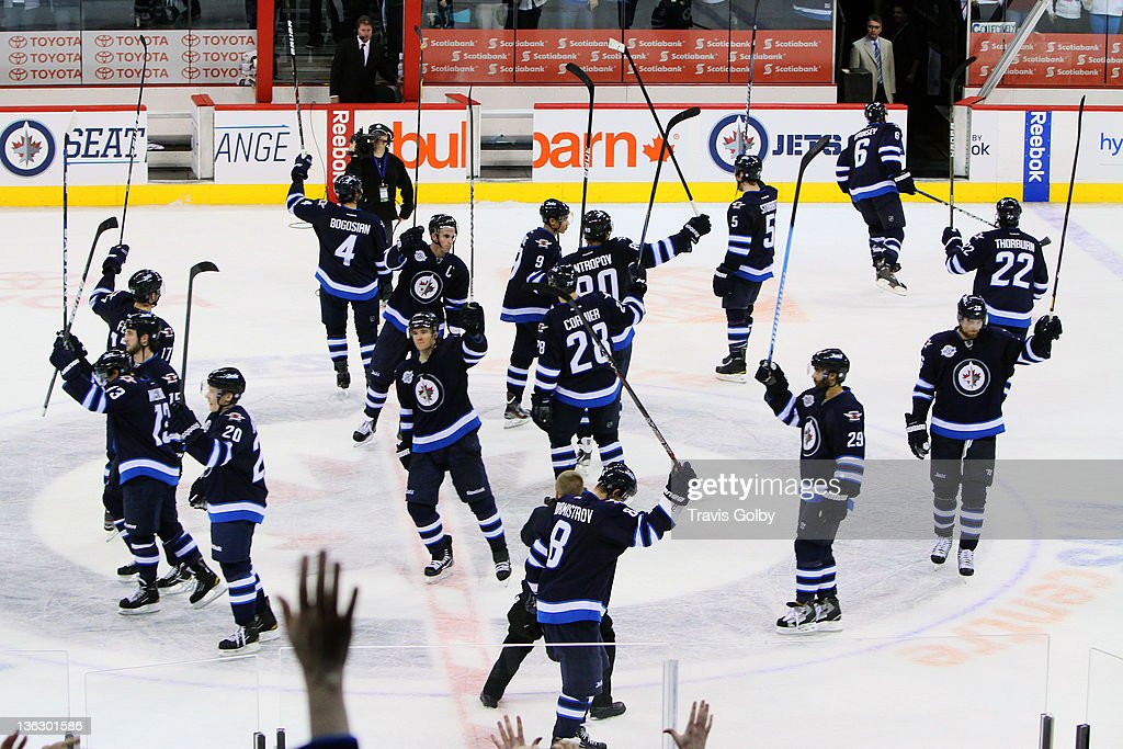 Members of the Winnipeg Jets salute the home fans following a 3-2 victory over the Toronto Maple Leafs at the MTS Centre on December 31, 2011 in Winnipeg, Manitoba, Canada.