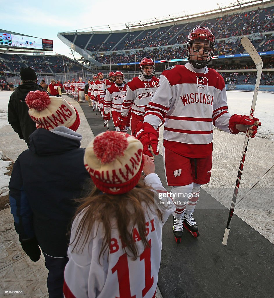 Members of the Wisconsin Badgers greet young fans in between periods against the Minnesota Golden Gophers during the Hockey City Classic at Soldier Field on February 17, 2013 in Chicago, Illinois.