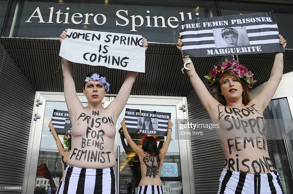 Members of the women's topless protest group Femen hold banners during a protest in front of the European Union Parliament on June 12, 2013 in Brussels, to support a detained Tunisian activist and four other Femen, two French and one German, arrested in Tunis for baring their breasts outside the main courthouse on May 29, in solidarity with a Tunisian activist who had been arrested 10 days earlier.
