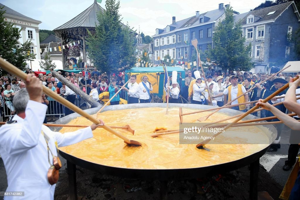 Members of the World Brotherhood of the Huge Omelet cook giant omlette within a 4 metre diameter frying pan in Malmedy, Belgium on August 15, 2017. Despite Insecticide-tainted eggs scandal in Europe, ten thousand eggs were used for the festival in Malmedy.