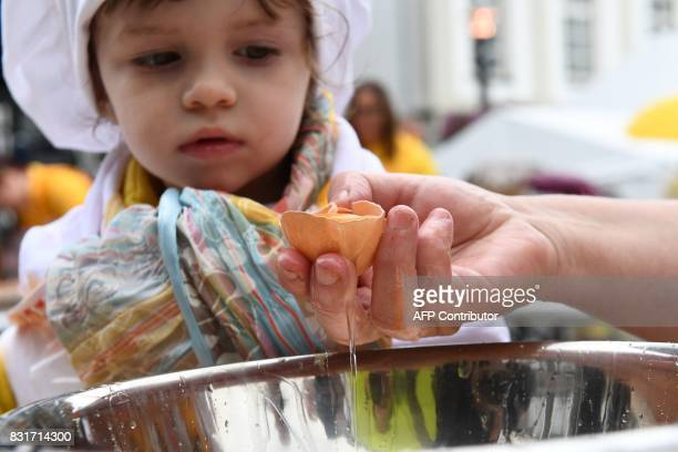 Members of the World Brotherhood of the Huge Omelet crack eggs to create a 6500 egg omelet on August 15 2017 in Malmedy Ten thousand hen's eggs will...