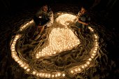 Members of the World Wildlife Fund sit among lit candles forming a representation of the Earth during a demonstration in a beach of Cancun on...