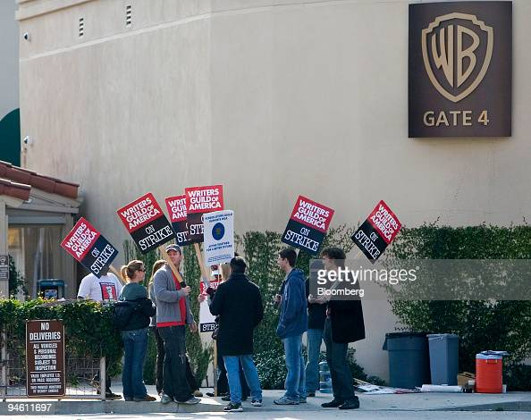 Members of the Writers Guild of America carry picket signs as they cross an intersection in front of Warner Bros Studios in Burbank California US on...