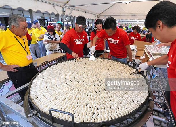 Members of the Yahata gyoza association prepare to serve the 1000 gyoza dumplings cooked on an iron pan measuring 13 meters in diameter on September...