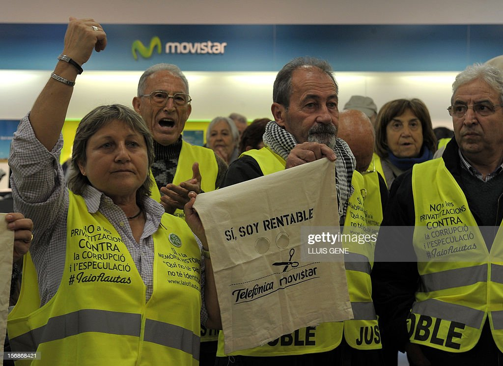 Members of the 'yayoflautas' organization hold a placard reading 'Yes, I'm profitable' as they occupy the headquarters of Spanish telecoms titan Telefonica (Movistar) on November 22, 2012 in Barcelona during a protest in support of Telefonica employees staging a hunger strike. Six Telefonica employees have been on a hunger strike since November 5 to protest the dismissal of two coworkers.