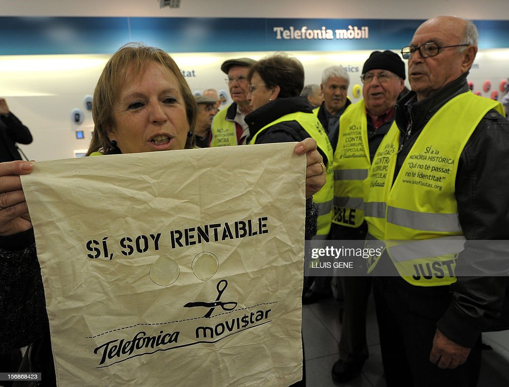 A members of the 'yayoflautas' organization holds a placard reading 'Yes, I'm profitable' during a protest in the headquarters of Spanish telecoms titan Telefonica (Movistar) on November 22, 2012 in Barcelona in support of Telefonica employees staging a hunger strike. Six Telefonica employees have been on a hunger strike since November 5 to protest the dismissal of two coworkers.