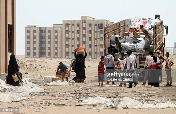 Members of the Yemeni Red Crescent distribute aid to displaced families in the alSaleh neighbourhood north of the southern Yemeni city of Aden on...