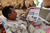 A members of the Yemeni Shiite Huthi movement reads a newspaper inside a tent on August 23 2014 at an encampment in northern Sanaa erected the...