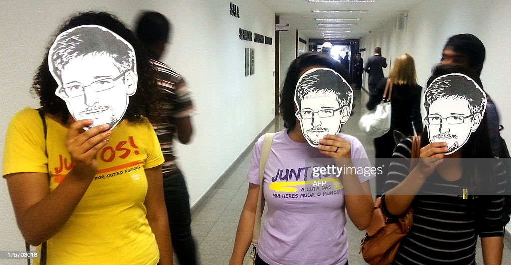 Members of the Youngs Together activist group pose with masks of Edward Snowden, former US National Security Agency contractor, during a public hearing of Brazil-based Guardian reporter Glenn Greenwald, at the Brazilian Senate's foreign relations committee, in Brasilia, on August 6, 2013. Greenwald was among the first to release details of Washington's vast electronic surveillance program, including Brazil, based on leaks from Snowden. Greenwald said that he had received more than 15,000 secret US government documents from intelligence leaker Snowden but gave no details of the content of the files. AFP PHOTO/Moises AVILA