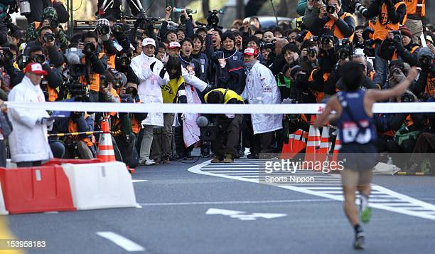 Members of Toyo University welcome the 10th and final runner Takashi Saito crossing the finishing tape during day two of the 88th Hakone Ekiden on...
