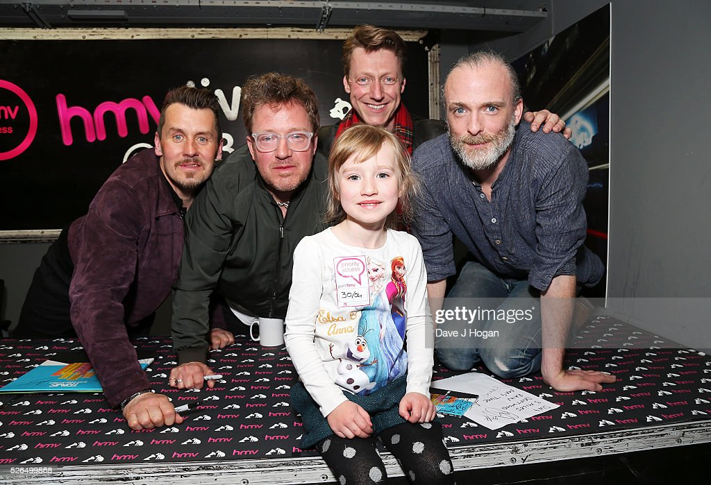 Members of Travis pose with a fan after performing songs from their new album 'Everything At Once' at HMV Oxford Street on April 30, 2016 in London, England.