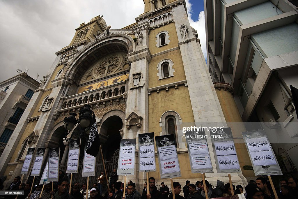 Members of Tunisian Islamist party Hizb-Ut-Tahrir hold Islamist flags and anti-France placards during a protest in front of the Cathedral of St Vincent de Paul near the French embassy in Tunis on February 14, 2013 in Tunis. Tunisia's ruling Ennahda party has called on supporters to rally Saturday and back its 'legitimacy' even as the prime minister, who belongs to the Islamist party, scrambles to form a new government of technocrats. AFP PHOTO/GIANLUIGI GUERCIA