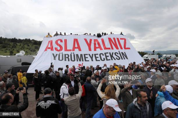 Members of Turkey's main opposition Republican People's Party hold a banner reading 'you will never walk alone' as CHP's leader gives his weekly...
