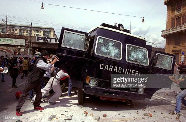 Members of Tutte Bianche attack a police vehicle during protests against the 27th Group of Eight Summit on July 20 2001 in Genoa Italy Hundreds of...