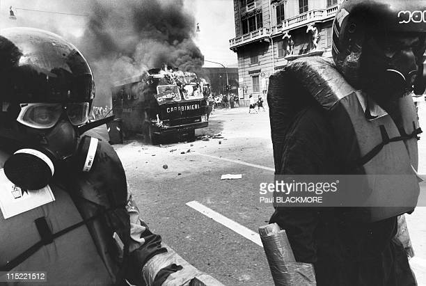 Members of Tutte Bianche walk away after setting an Italian police vehicle on fire during protests against the 27th Group of Eight Summit in July...