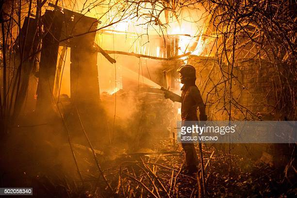 TOPSHOT A members of UME tries to put out a wild fire in Carrio northwest Spain on December 20 2015 Some 230 firefighters were dispatched to battle...