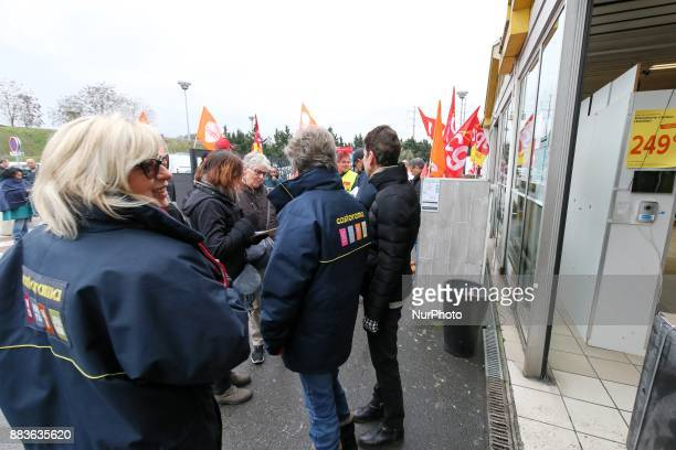 Members of unions gather in front of a French tools and supplies retailer Castorama store in Creteil East of Paris on December 1 to protest against...