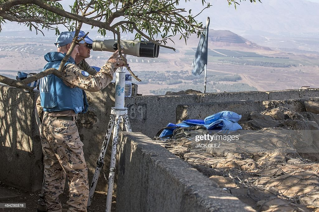 Members of United Nations Disengagement Observer Force Zone (UNDOF) use binoculars to watch smoke rising in the distance caused by fighting between forces loyal to Syrian President Bashar Assad and rebels over the control of the Quneitra border crossing, on August 27, 2014. Syrian rebels, including Al-Qaeda's affiliate Al-Nusra Front, seized control of the Syrian crossing with the Israeli-occupied Golan Heights today, the Britain-based Syrian Observatory for Human Rights said.